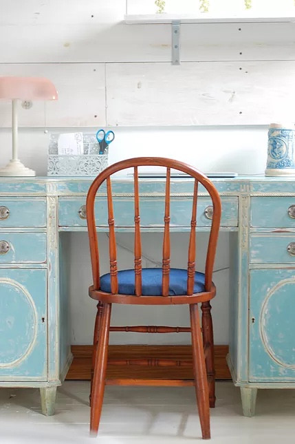 A chair tucked under a robin's egg blue distressed desk.