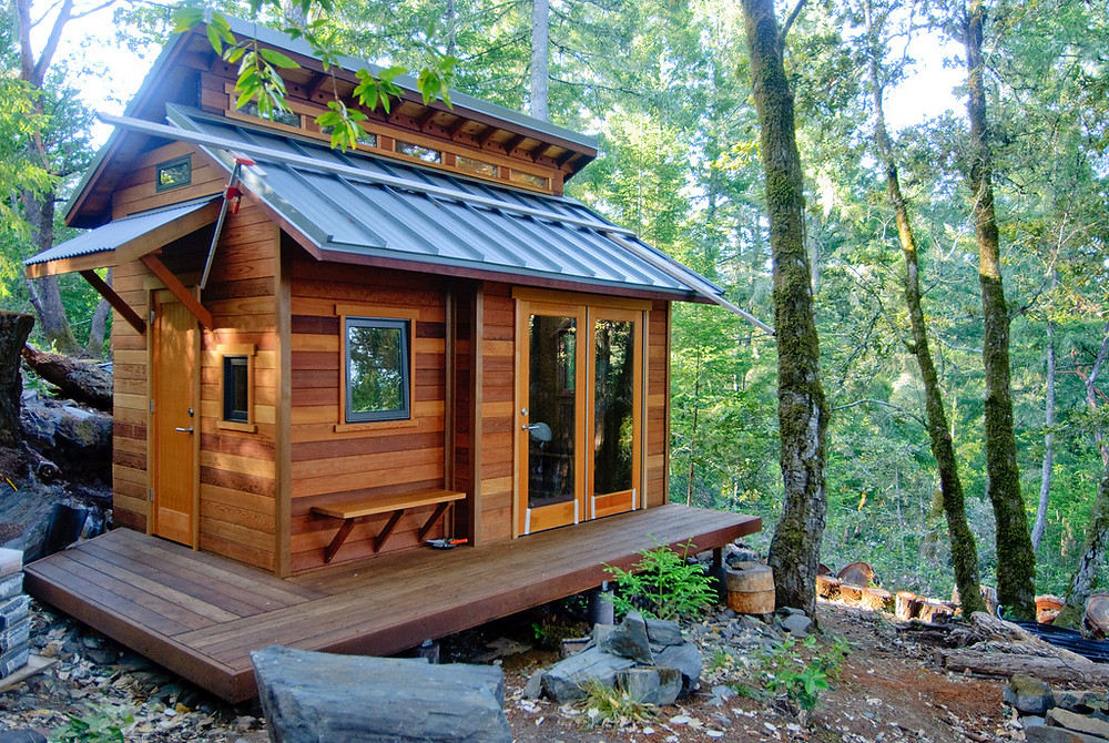 A rustic tiny house surrounded by woods.