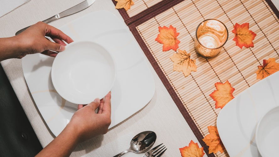 A person arranging dinnerware on a table for Thanksgiving.