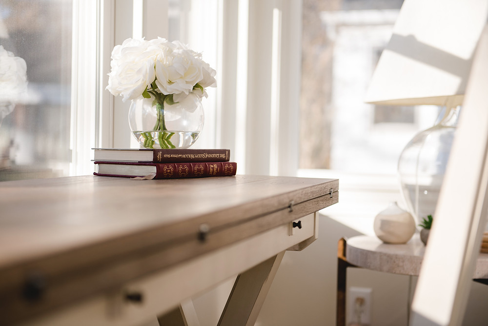 A desk with an artistic display of flowers and books arranged by LF Designs.