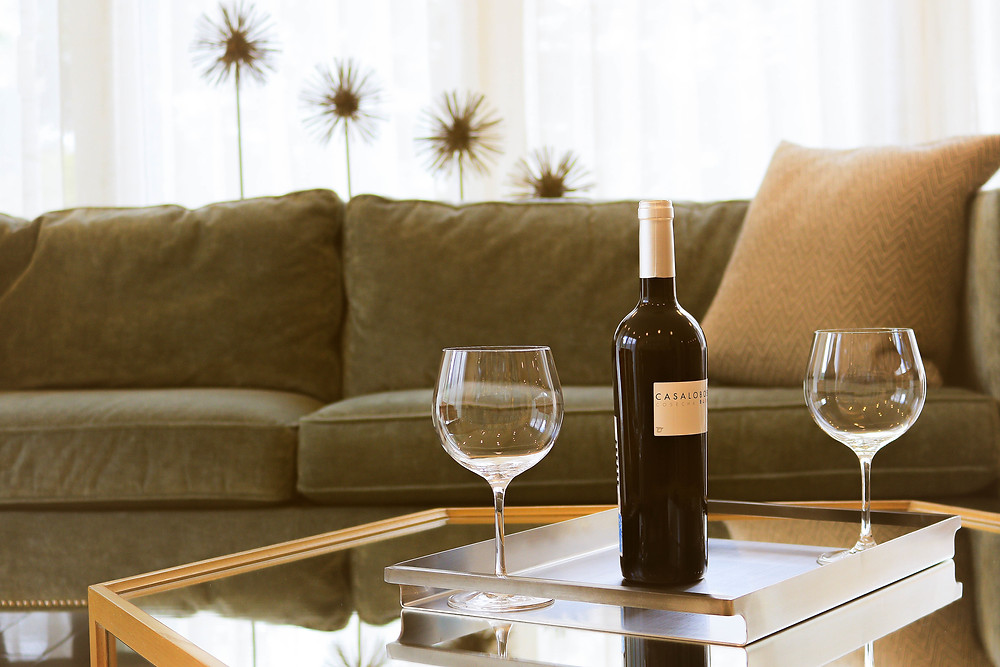 A coffee table makes wine glasses easily reachable from a couch.
