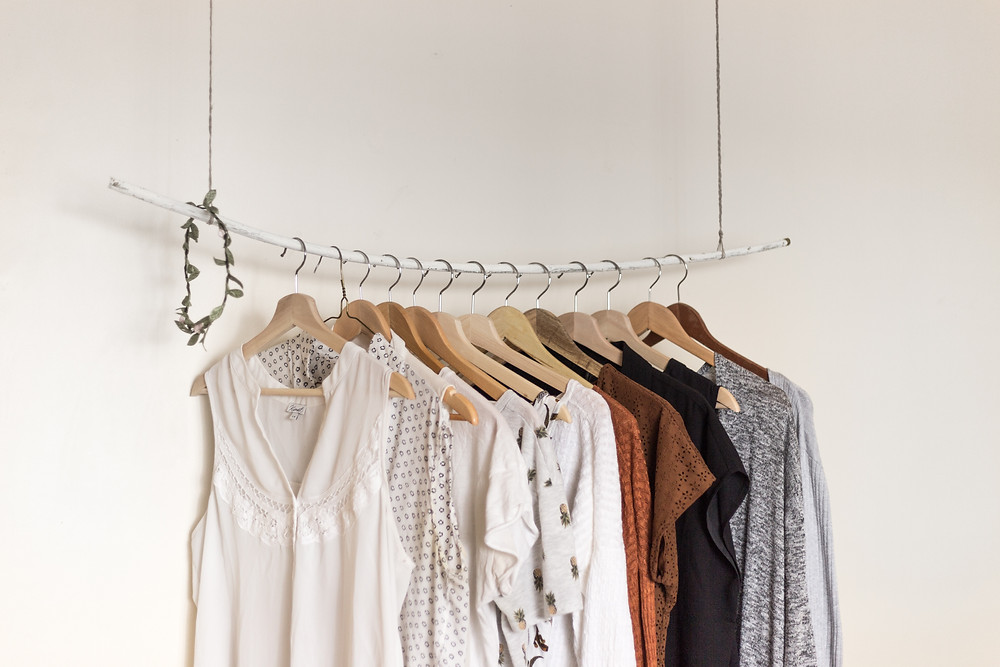 A row of shirts hanging against a white wall.