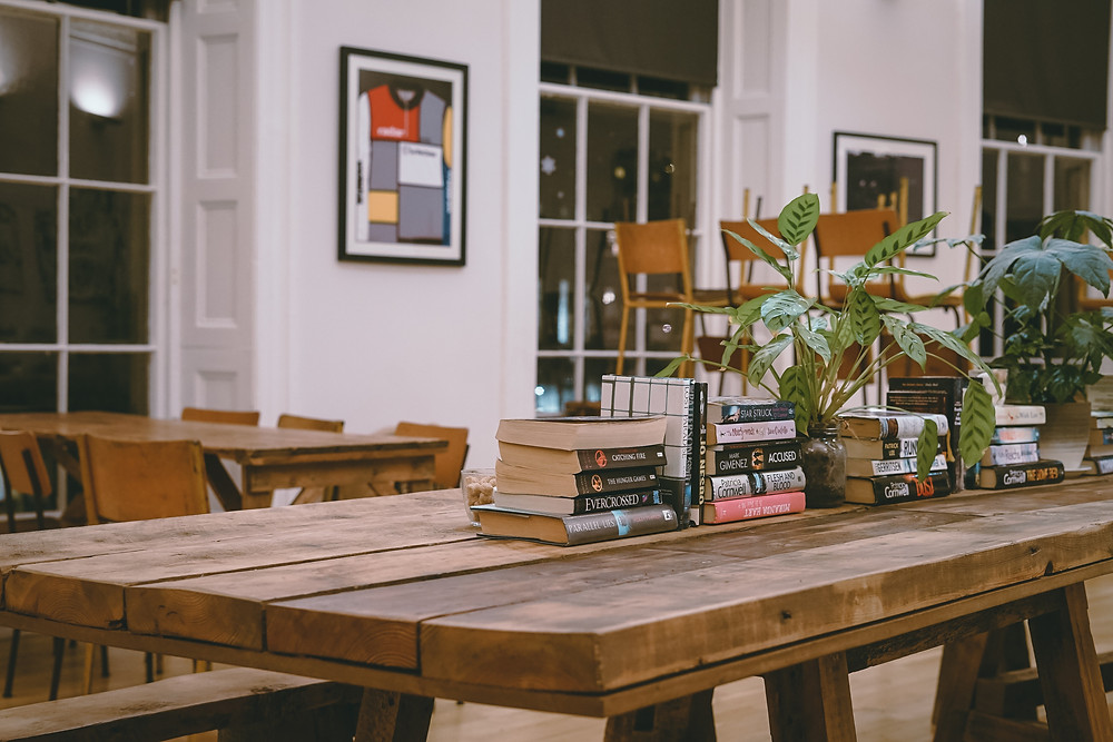 A large table with a centerpiece consisting of stacks of books and houseplants.