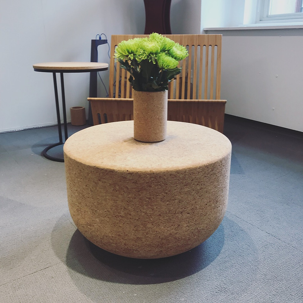 A table and chair display at NeoCon with a vase of green flowers acting as the accent.