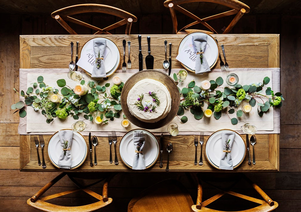 A natural Thanksgiving tablescape featuring greenery, candles, and neutral colors.