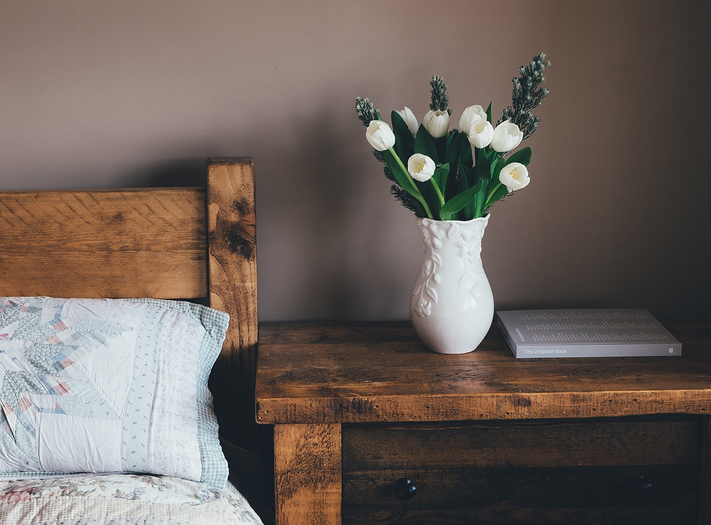 A rustic bed set with a vase of flowers on the nightstand.