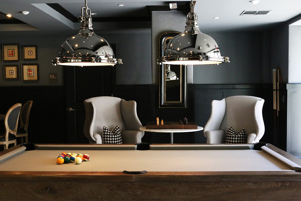 Two chairs are grouped around a small table and face a pool table.