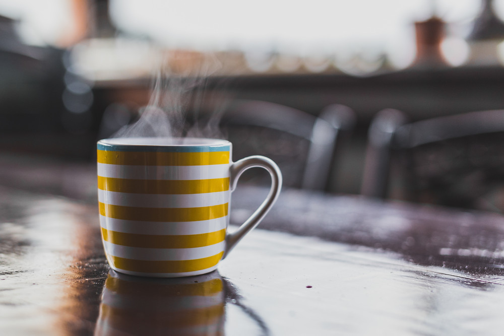 A steaming hot toddy in a yellow and white striped mug.