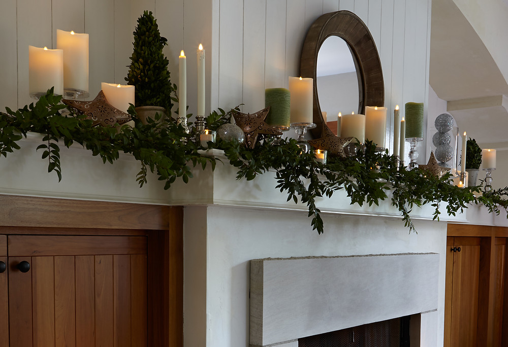 A mantel decorated with Luminara candles and greenery.