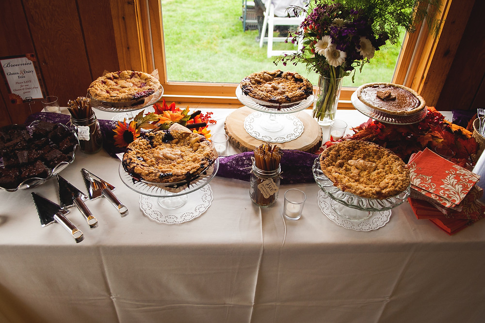A dessert table with natural decorations mixed in.