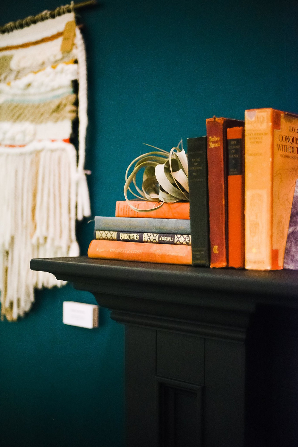 Books beautifying a mantel in a space by Lauren Figueroa.