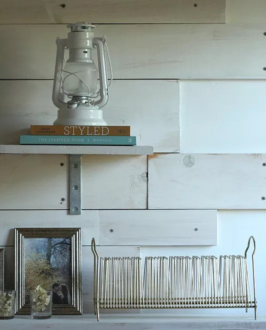 Shelves decorated with a lantern, books, a picture frame, and votive holders.