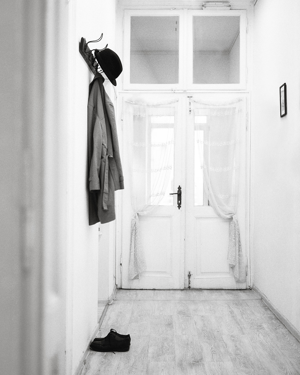 A black and white photo of a foyer with coat hooks and shoes.