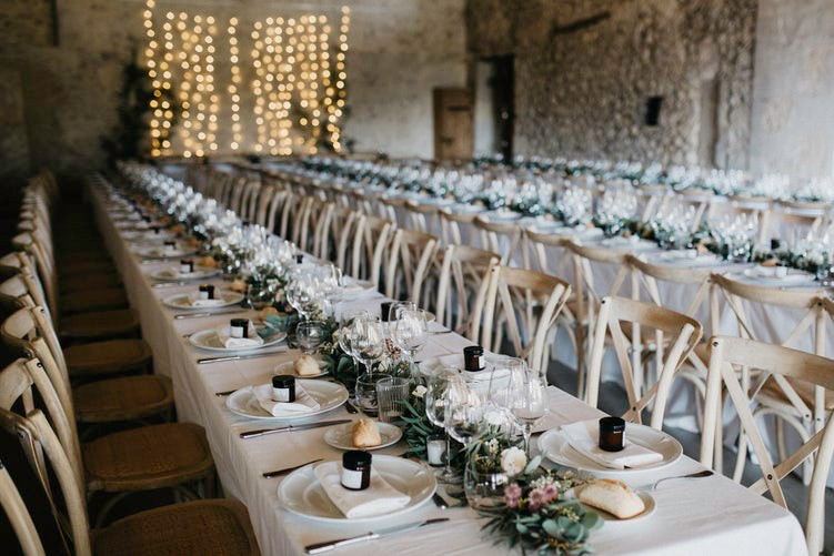 Two long buffet tables decorated with winding greenery.