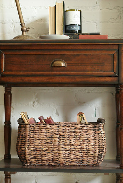 A wooden accent table with a woven basket beneath it.