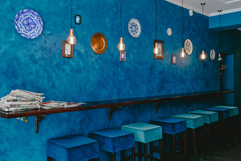 A cafe with blue walls and blue stools.