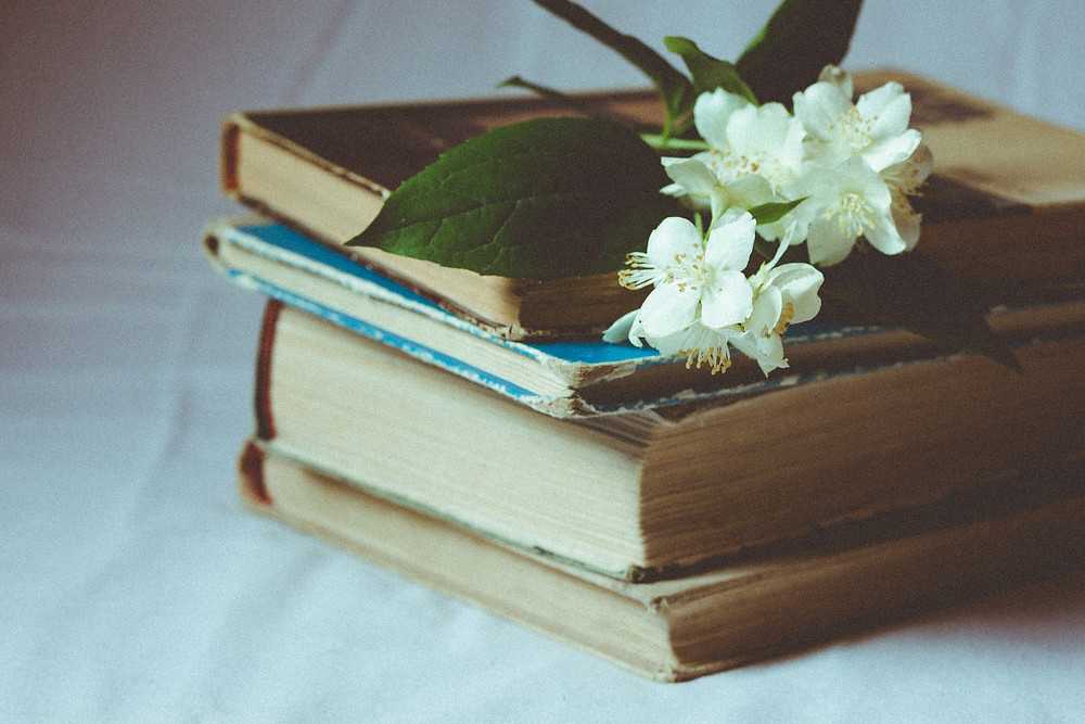 A stack of aged books topped with flowers.