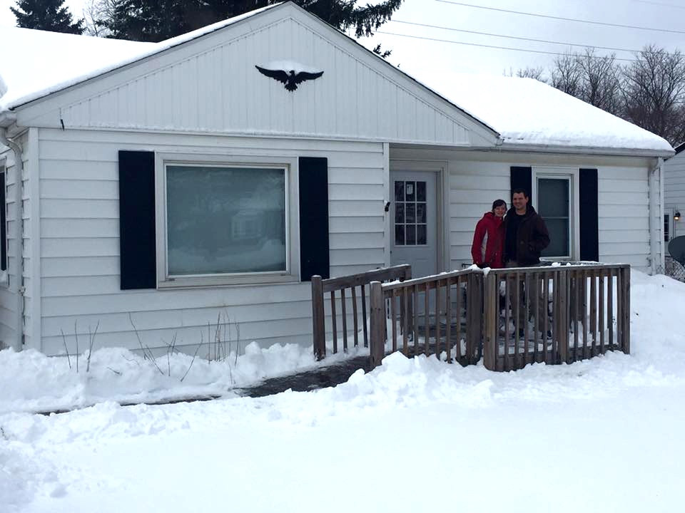A small ranch house covered in snow.