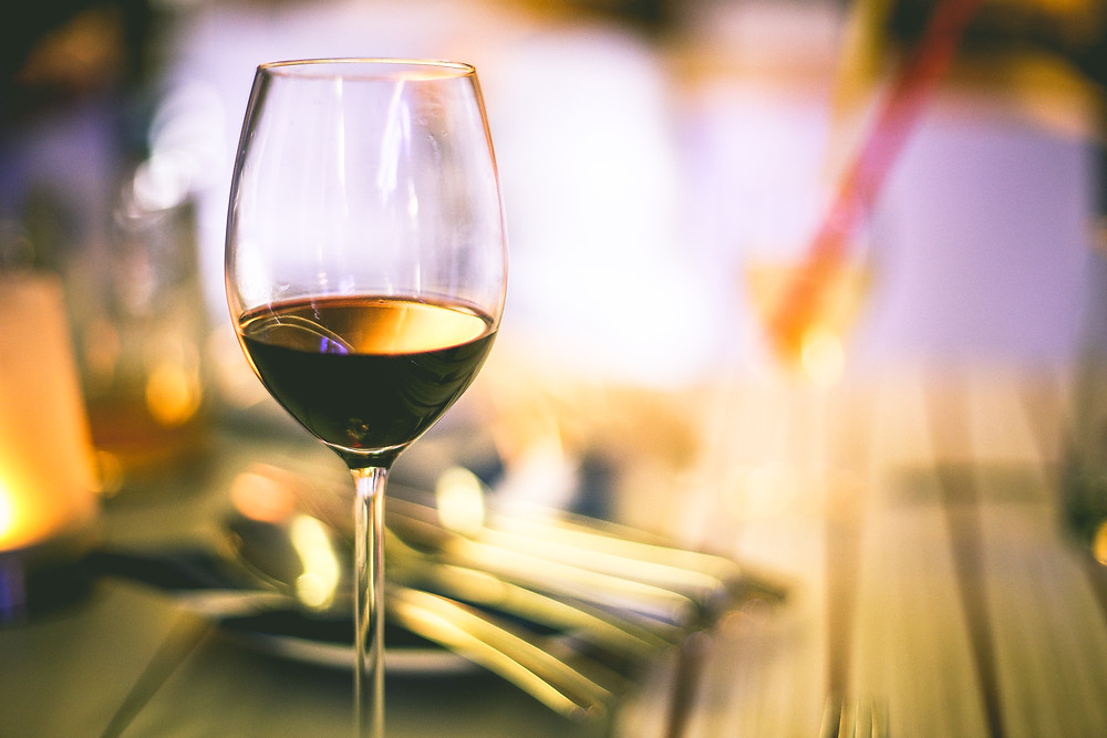 An image of a half full glass of wine on a table.