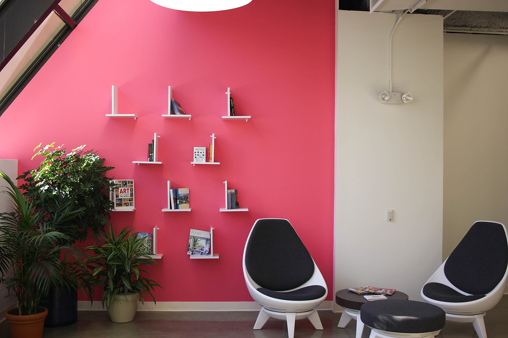 Small modern bookshelves on a red wall.