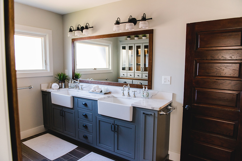 The vanity complete with farmhouse sinks and a large mirror.