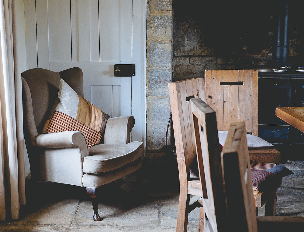 Rustic wooden chairs are gathered around a dining room table.