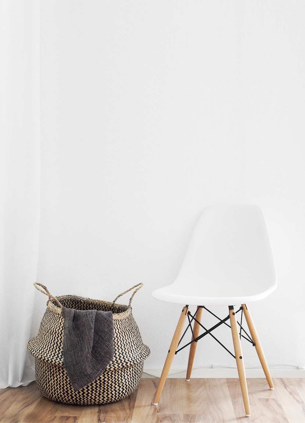 A smooth plastic chair beside a woven basket.