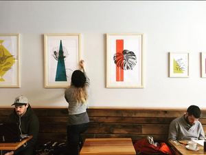 A woman hanging artwork at Rowster Coffee.