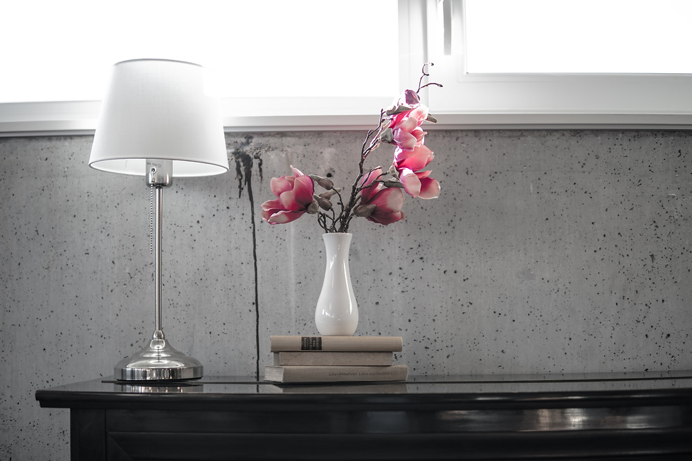 A vase of flowers and a lamp in a foyer.