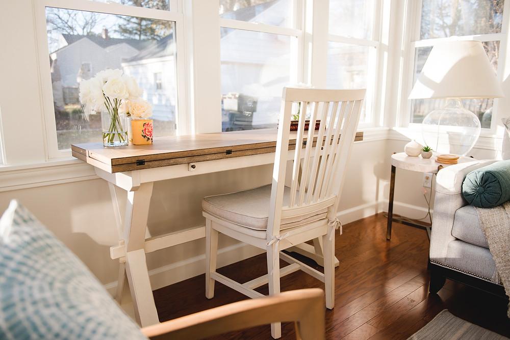 A white desk in the four season room.