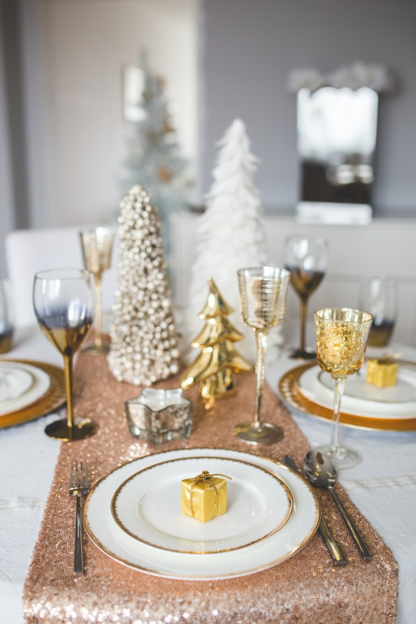 A gold and silver themed centerpiece with decorative glass trees and a sparkling table runner.