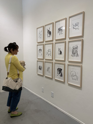 Lisa Solomon looking at Kristina's Micotti's show of dog portraits in the Long Weekend Gallery.