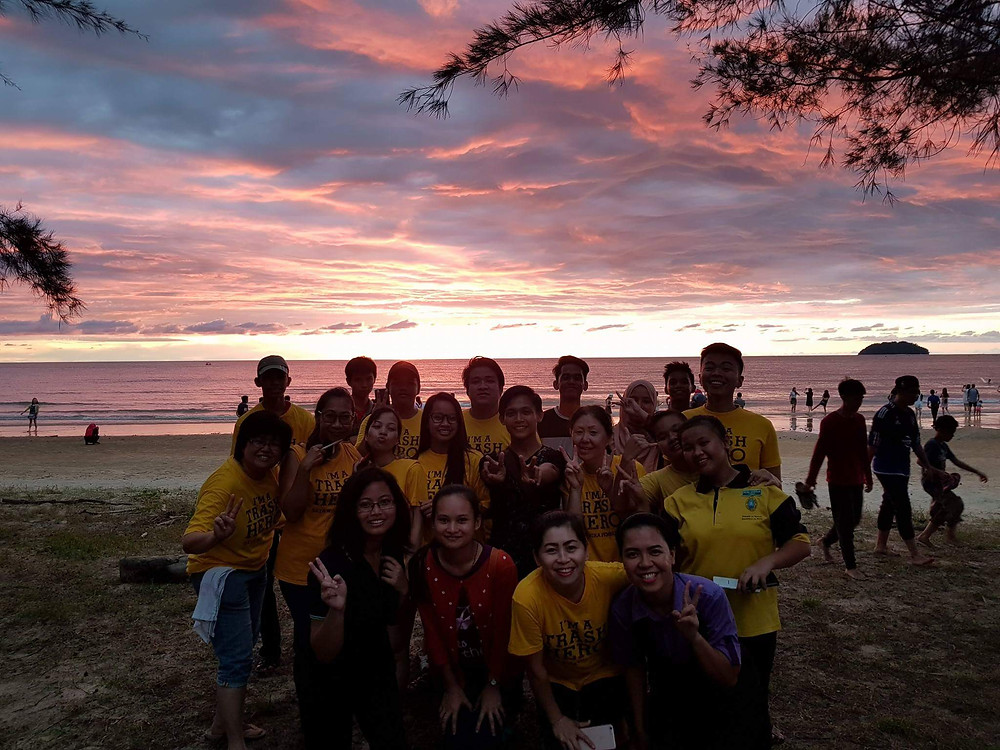 Group photo with beautiful sunset after cleanup