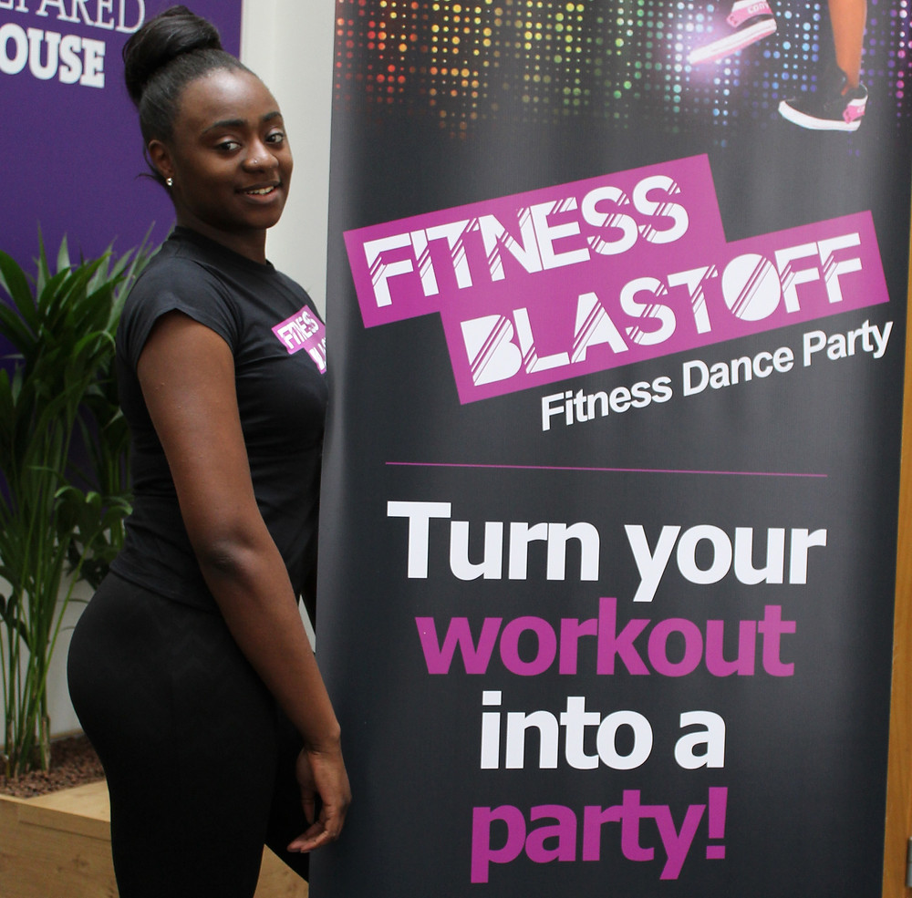 Renee posing next to the Fitness Blastoff Banner