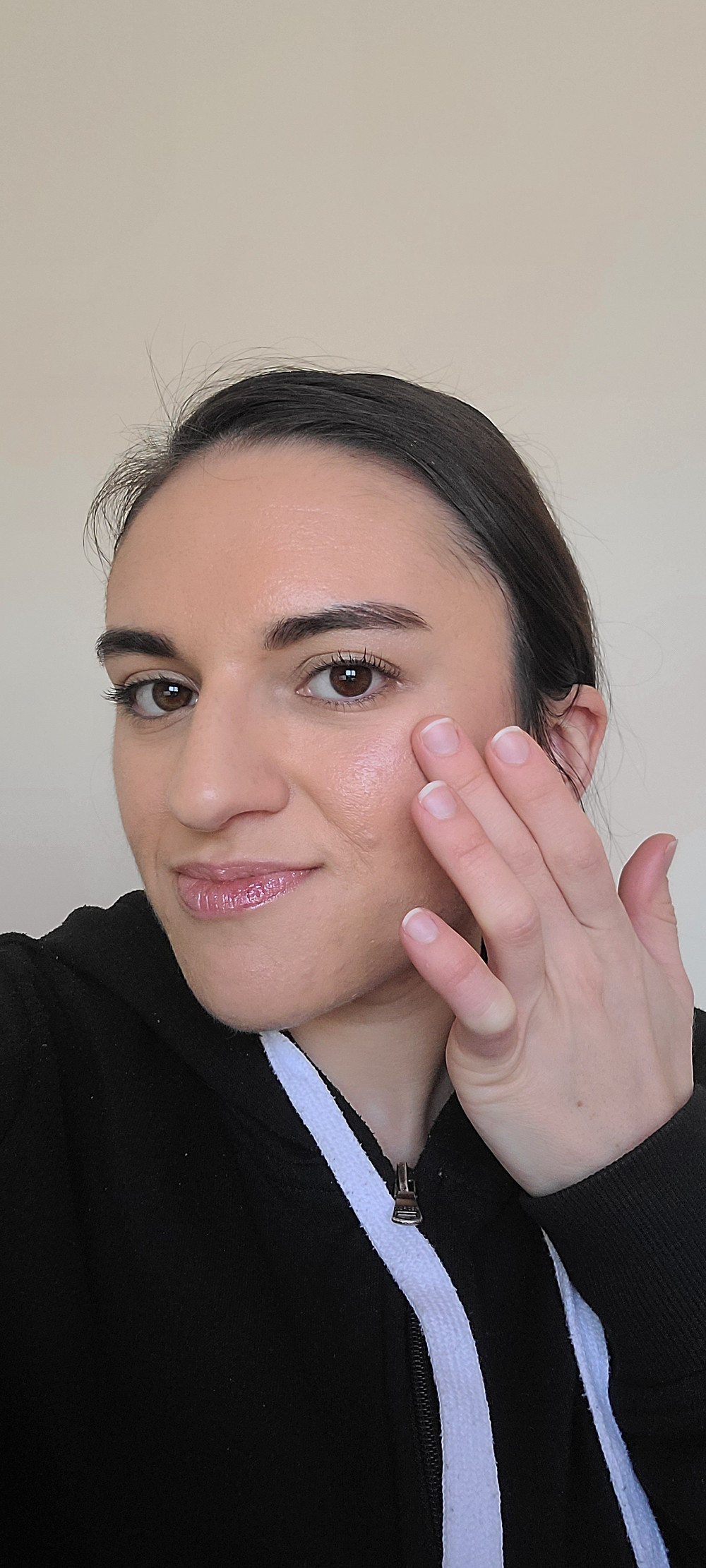 Carla is applying highlighter to her cheek bone with her ring finger.