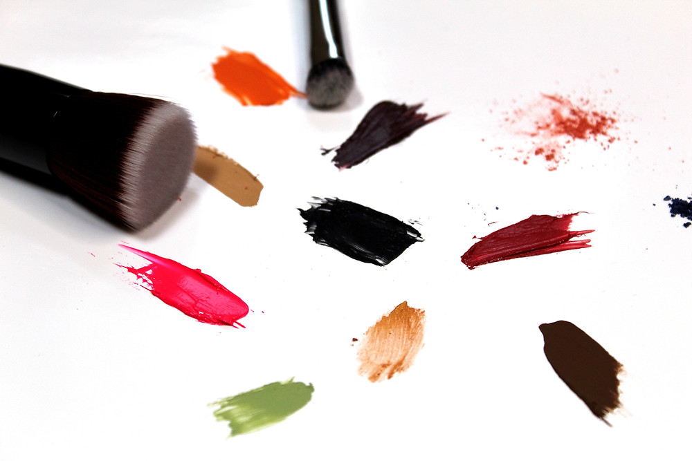 makeup brushes and smeared makeup products on a piece of paper