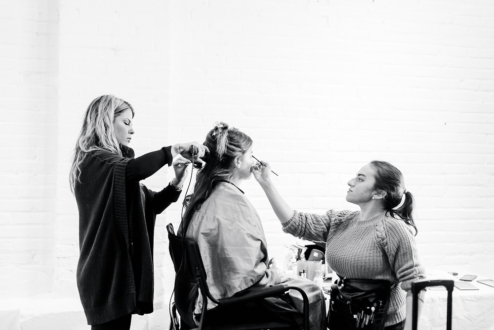 Carlla adusting eye makeup on model while hair stylist is curling model's hair.