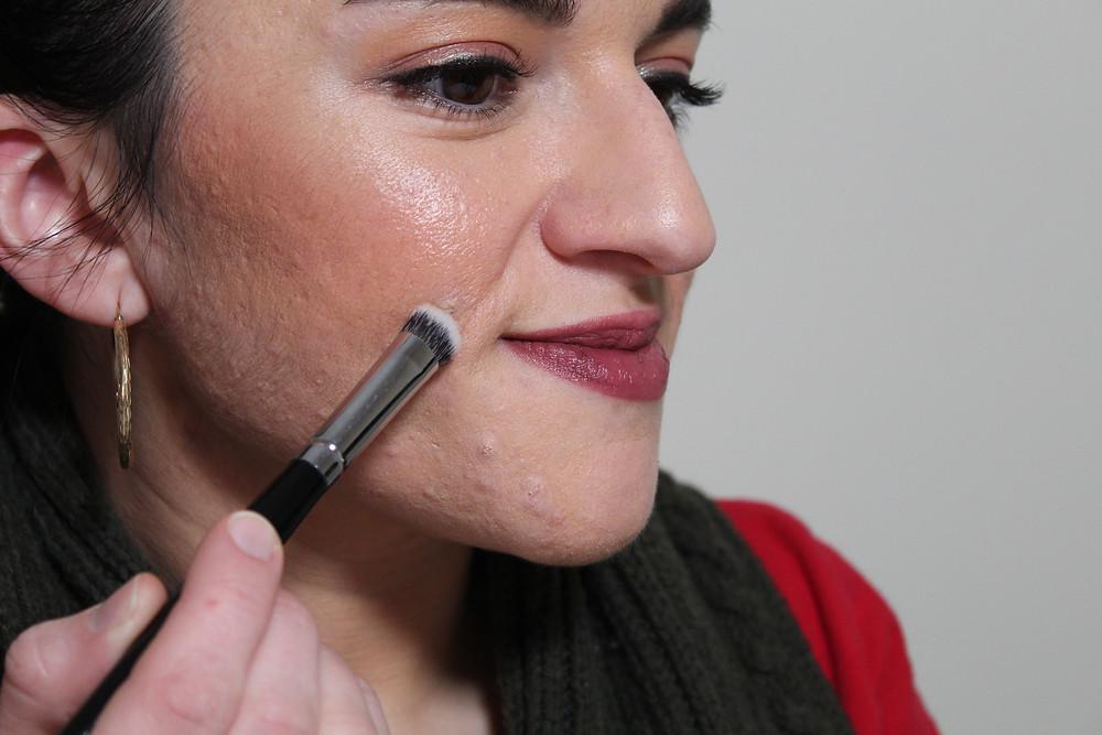 Carla using a makeup brush to apply makeup