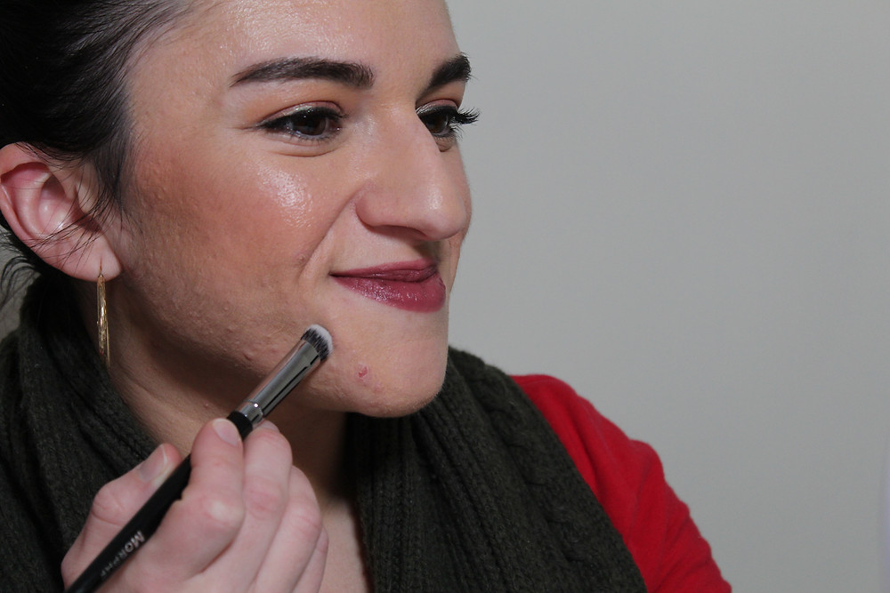 Carla using a makeup brush to cover a pimple