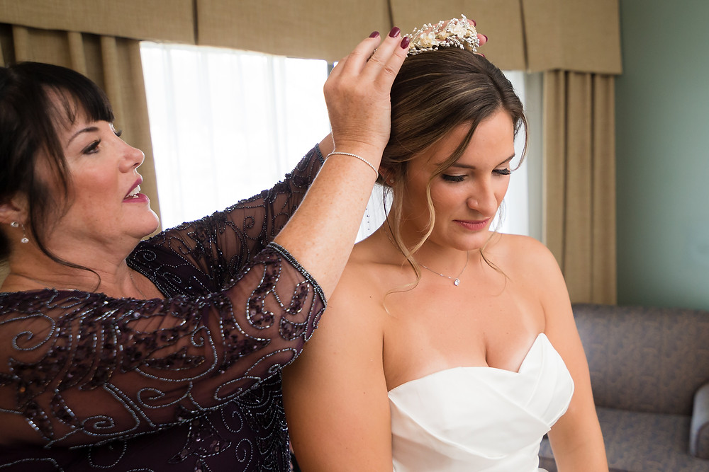 Mother helping bride put on flower crown