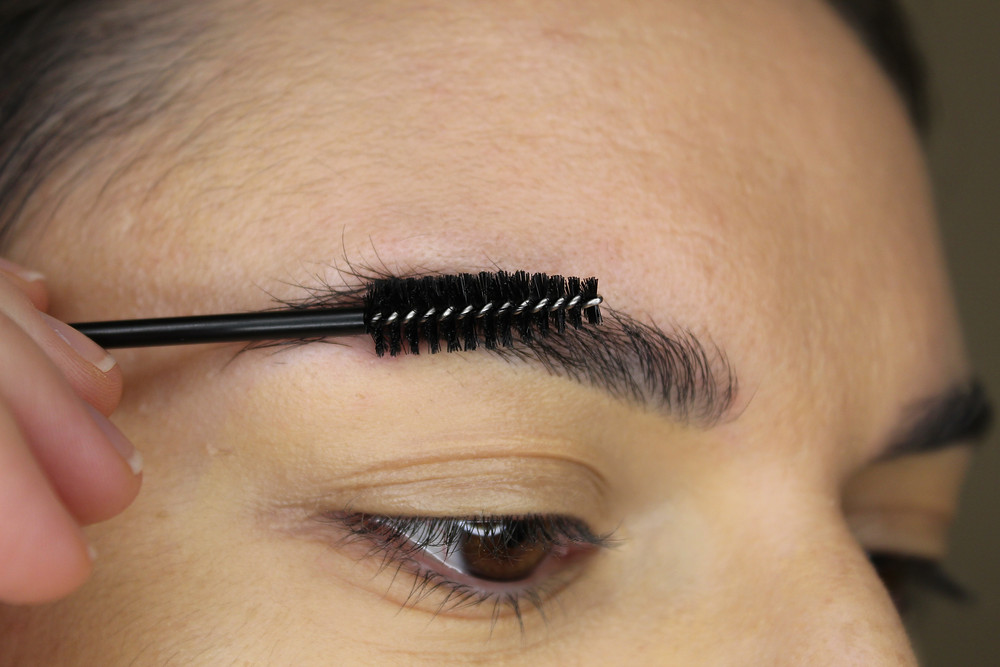 Brushing eyebrow hair.