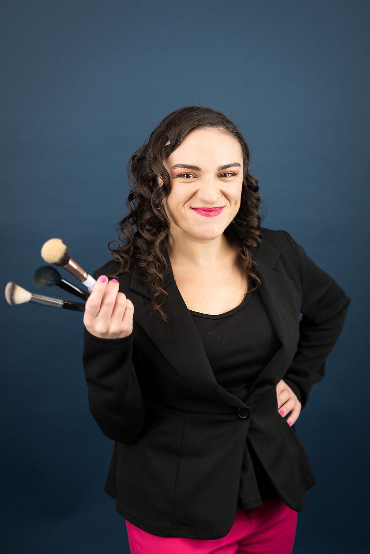 Carla posing while holding makeup brushes
