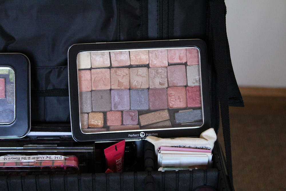 eyeshadow palette is standing up against a suitcase