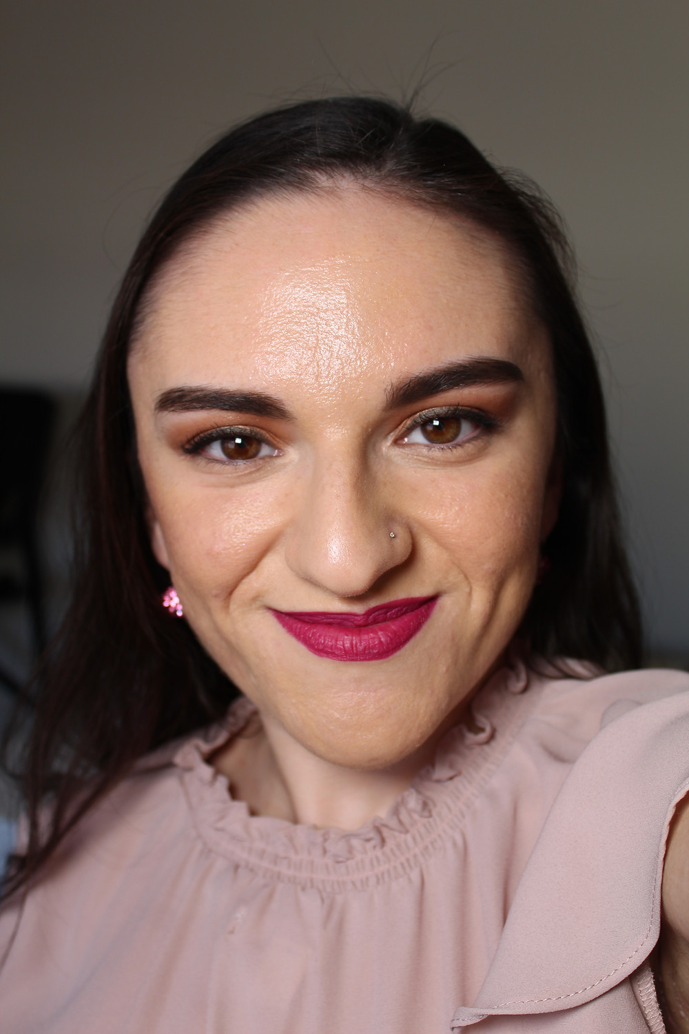 Carla is posing with a smirk to show off her makeup.