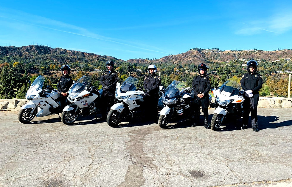 Team of motor escorts / motorcade officers lined up in front of a hillside residential background.