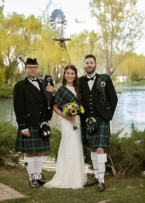 Groom and bride posing for a photo with a bagpiper dressed in traditional Scottish kilt uniform and suit.