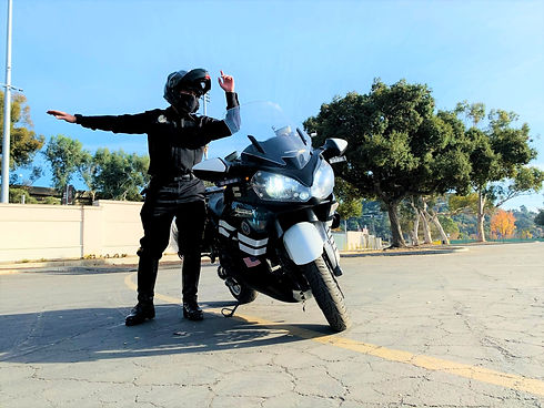 A male motor escort / motorcade officer directing traffice next to his motorcycle.
