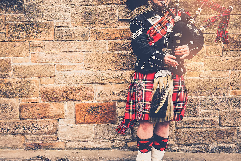 Scottish bagpiper dressed in traditional red and black uniform