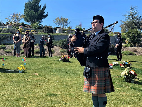 Traditional Irish kilted bagpiper palying at a funeral and celebration of life.
