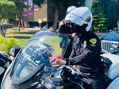 A uniformed motor escort officer inputting GPS directions on his motorcycle.